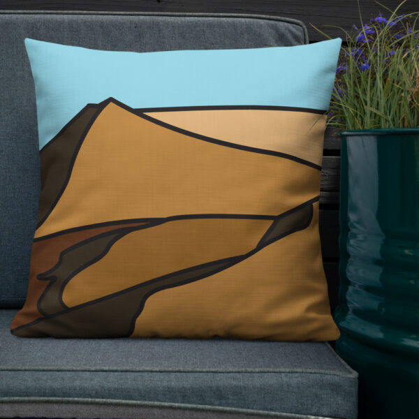 square pillow with a minimalist desert sand dune landscape design sitting on a chair next to a plant