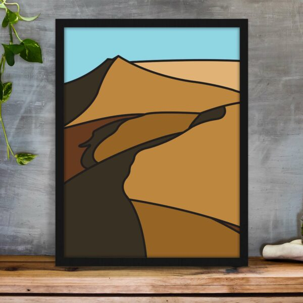 vertical fine art print with a minimalist sand dune design in a black frame on a table