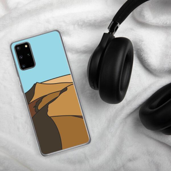 samsung phone case with a minimalist desert landscape design sitting next to headphones