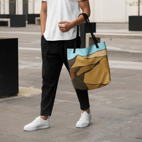 person holding a tote bag with black handles and a minimalist desert landscape design