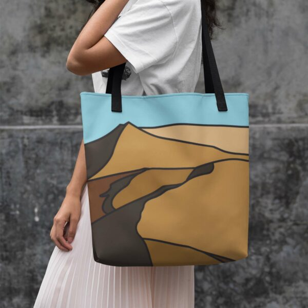 woman holding a tote bag with black handles and a minimalist desert landscape design