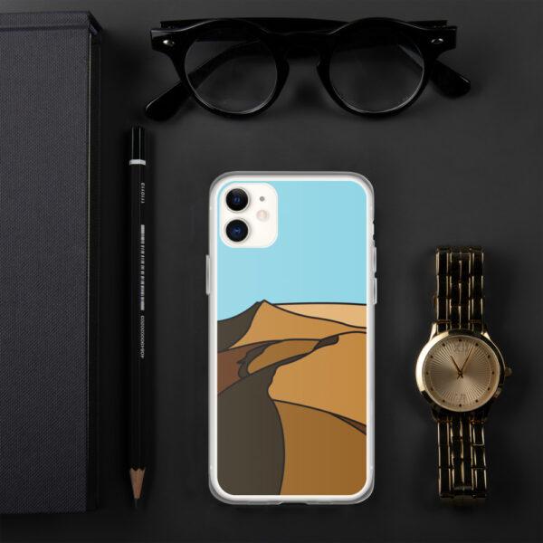 iphone case with a minimalist desert landscape design sitting next to a watch
