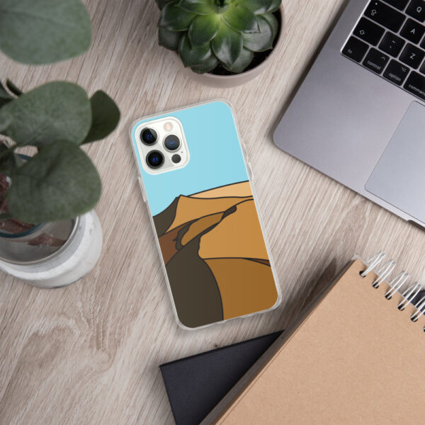 iphone case with a minimalist desert landscape design sitting next to a laptop