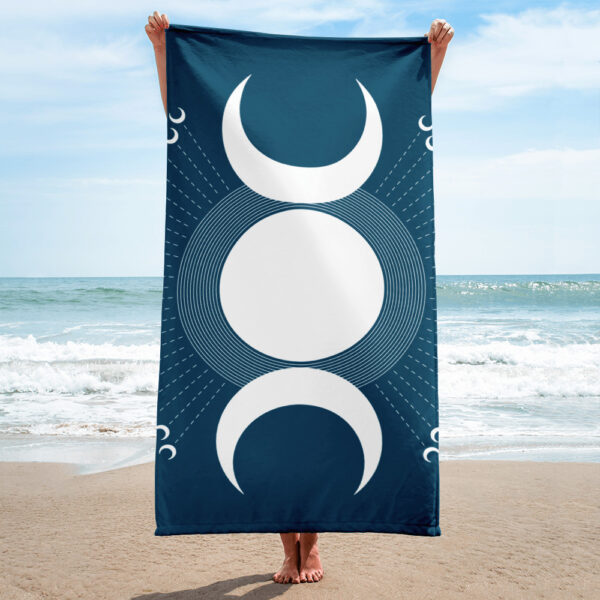 person on a beach holding a beach towel with a white moon design on blue background