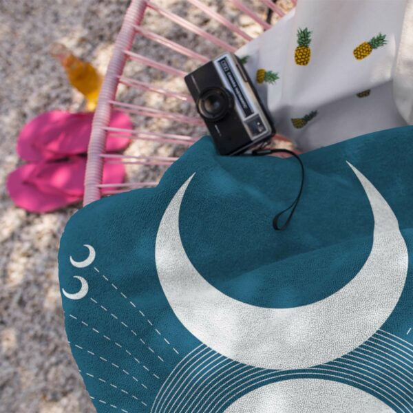 beach towel with a white moon design on blue background next to a camera