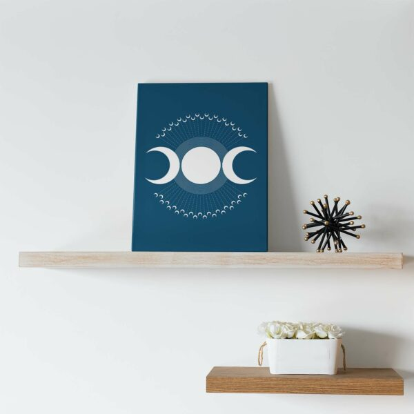 vertical stretched canvas print with a design of three white moon phases on a blue background sitting on a shelf