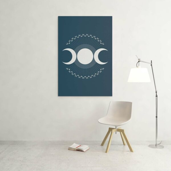 large vertical stretched canvas print with a design of three white moon phases on a blue background hanging on a wall