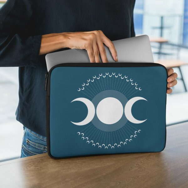person holding a laptop sleeve with three white moons on a dark blue background