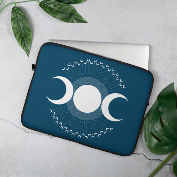 laptop sleeve with three white moons on a dark blue background sitting on a table