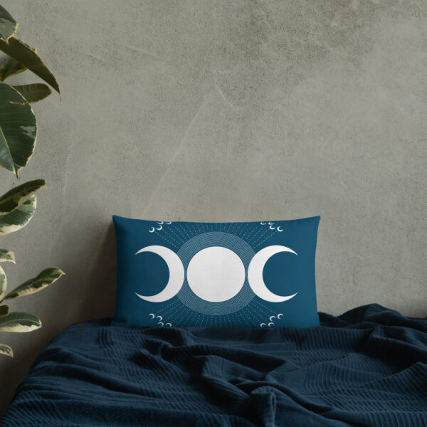 rectangle pillow with three white moons on a dark blue background sitting on a bed