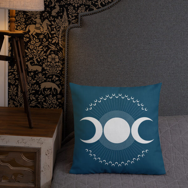 square pillow with three white moons on a dark blue background sitting on a bed
