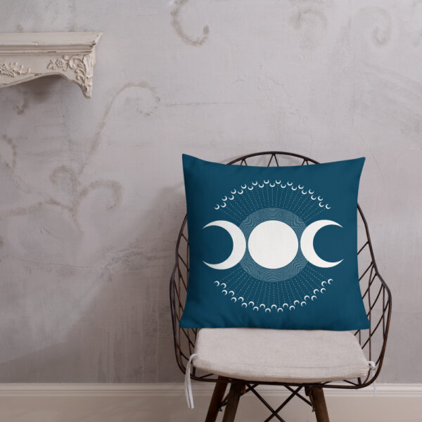 square pillow with three white moons on a dark blue background sitting on a chair