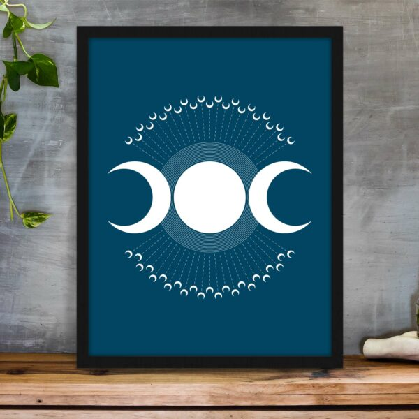 vertical fine art print with three white moons on a dark blue background in a black frame on a table