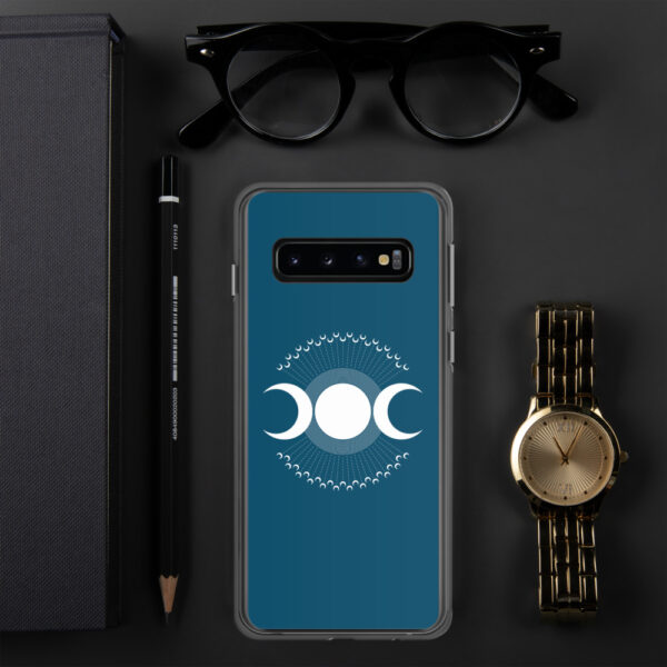 samsung phone case with three white moons on a blue background sitting next to a watch