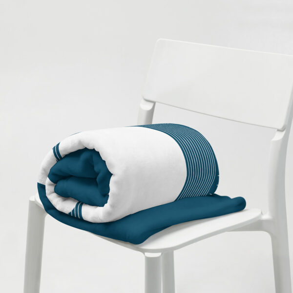 dark blue blanket with three large white moons and many smaller white moons, rolled up on a chair