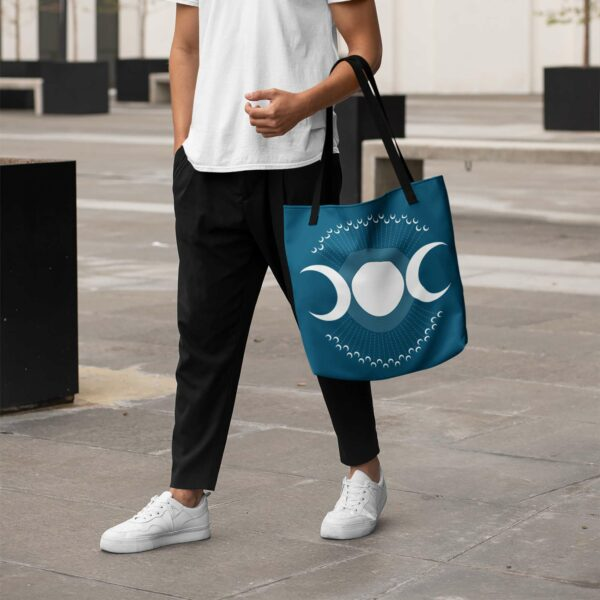 person holding a blue tote bag with black handles and a design of three white moon phases surrounded by smaller moons