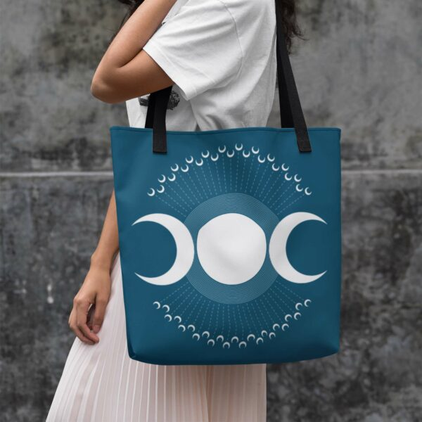 woman holding a blue tote bag with black handles and a design of three white moon phases surrounded by smaller moons