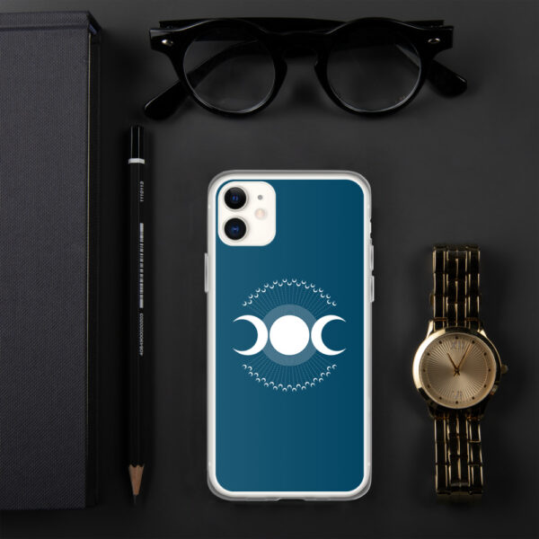 iphone case with three white moons on a blue background sitting next to a watch