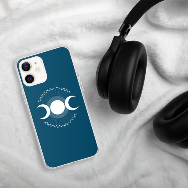 iphone case with three white moons on a blue background sitting next to headphones