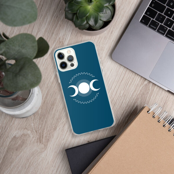 iphone case with three white moons on a blue background sitting next to a laptop