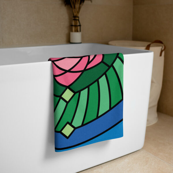 beach towel with a colorful pink and green lotus flower design draped on a bathtub
