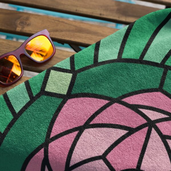 beach towel with a colorful pink and green lotus flower design next to sunglasses