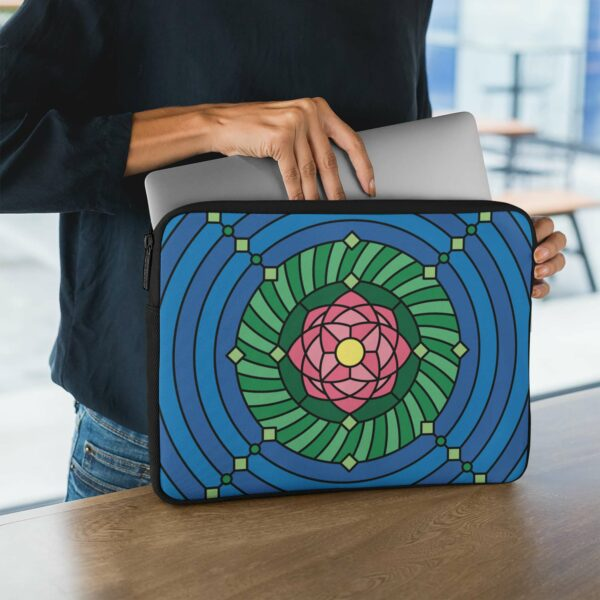 person holding a laptop sleeve with a colorful pink green and blue lotus flower design