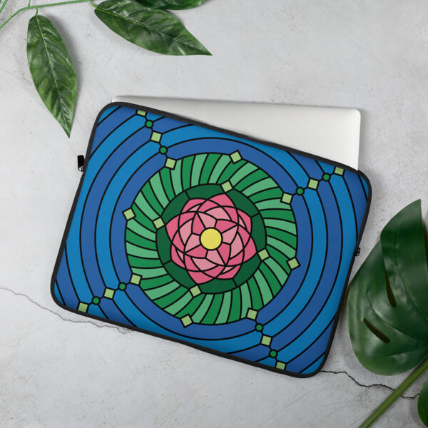 laptop sleeve with a colorful pink green and blue lotus flower design sitting on a table