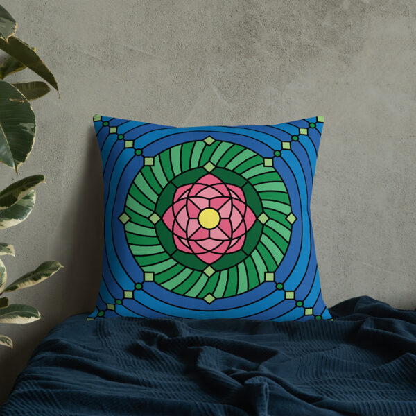 square pillow with a pink green and blue lotus flower design sitting on a bed