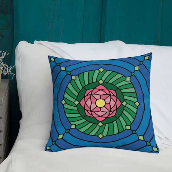 square pillow with a pink green and blue lotus flower design sitting on a sofa