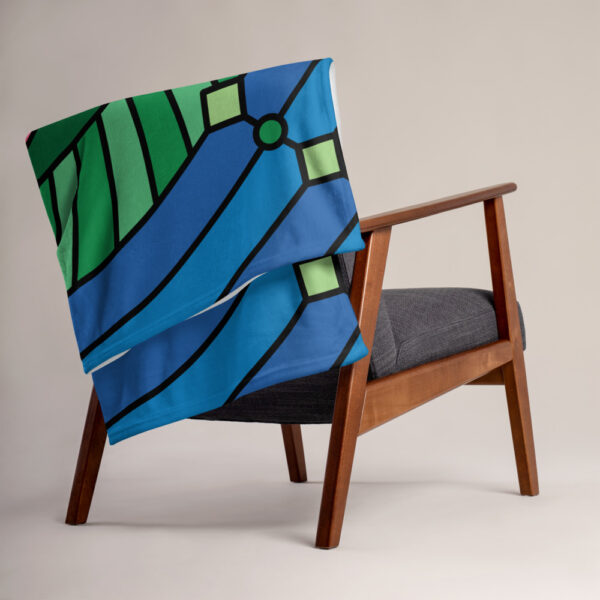 blanket with a colorful pink green and blue lotus flower design, draped over a chair