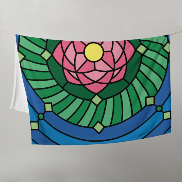 blanket with a colorful pink green and blue lotus flower design, hanging on a clothes line
