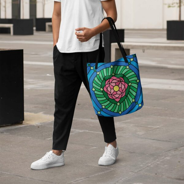 person holding a tote bag with black handles and a pink green and blue lotus flower design