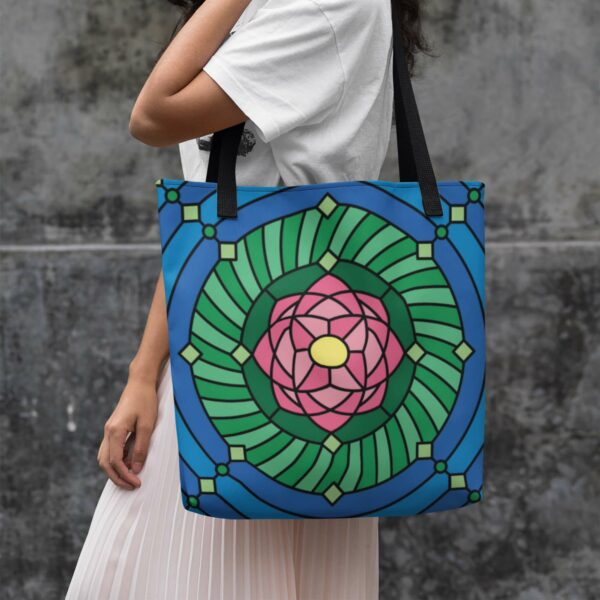 woman holding a tote bag with black handles and a pink green and blue lotus flower design