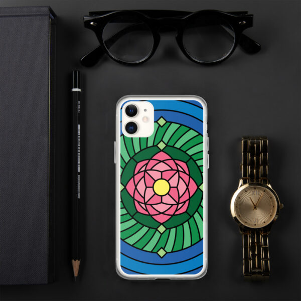 iphone case with a pink green and blue lotus flower illustration sitting next to a watch