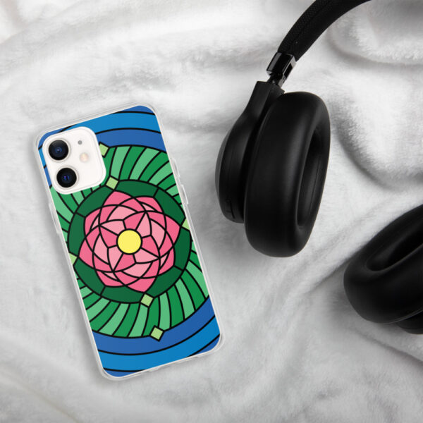 iphone case with a pink green and blue lotus flower illustration sitting next to headphones