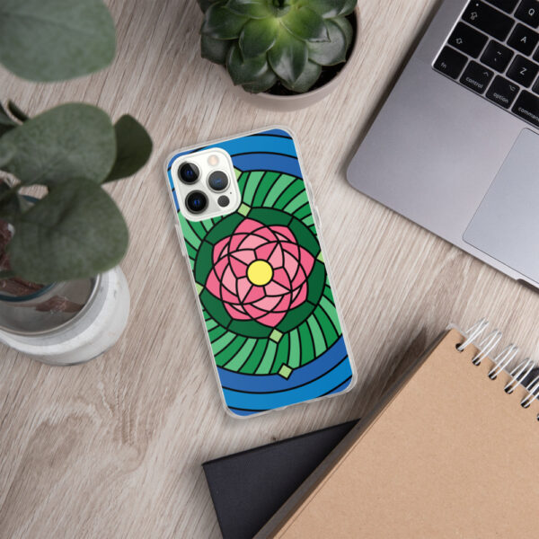iphone case with a pink green and blue lotus flower illustration sitting next to a laptop