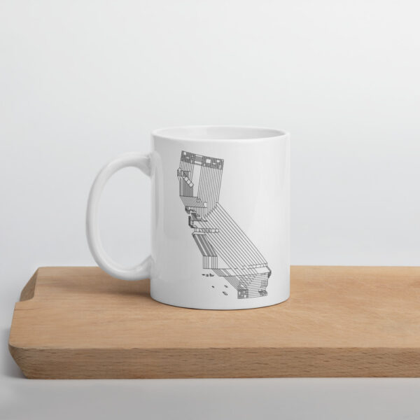 11 ounce white ceramic coffee mug with a black line drawing of the state of california on the side sitting on a cutting board