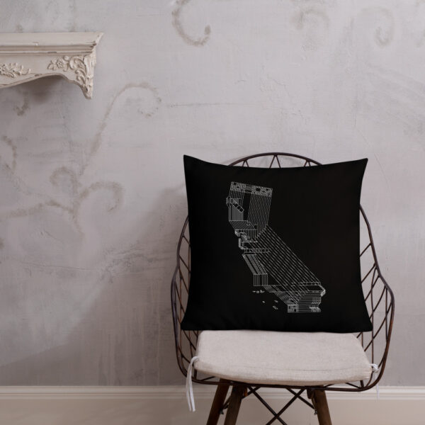 square black pillow with a white line drawing of the state of california, sitting on a chair