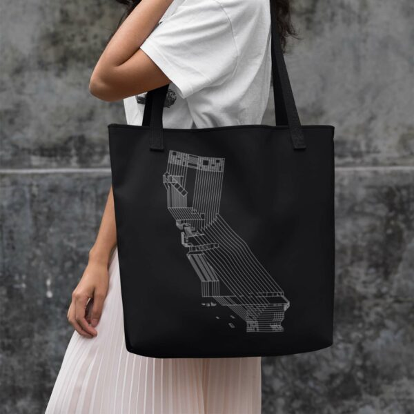 woman holding a black tote bag with black handles and white line drawing of the state of california