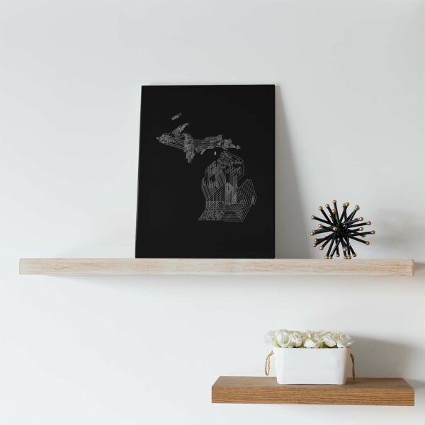 vertical stretched canvas art print of a white line drawing of the state of michigan on a black background sitting on a shelf