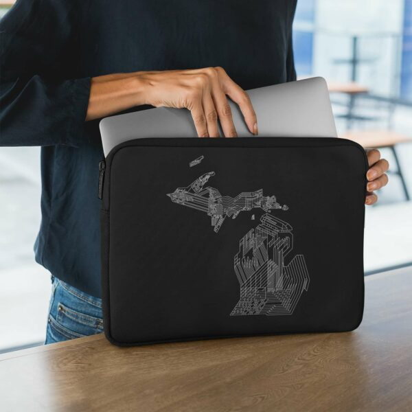 person holding a laptop sleeve with a white line drawing of the state of michigan on a black background