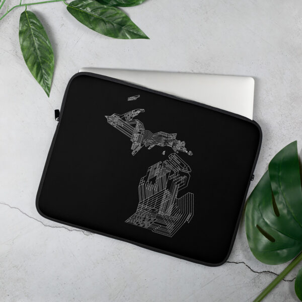 laptop sleeve with a white line drawing of the state of michigan on a black background sitting on a table