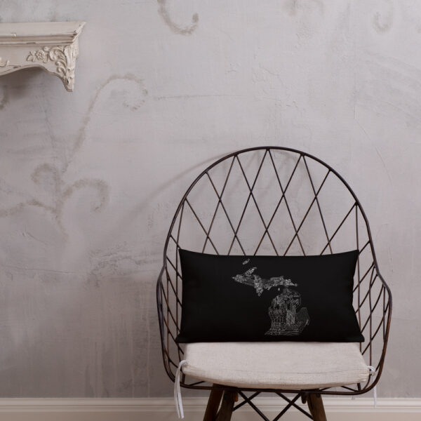 rectangle black pillow with a white line drawing of the state of michigan, sitting on a chair