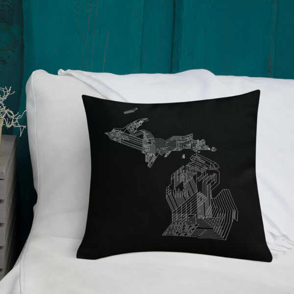 square black pillow with a white line drawing of the state of michigan, sitting on a sofa