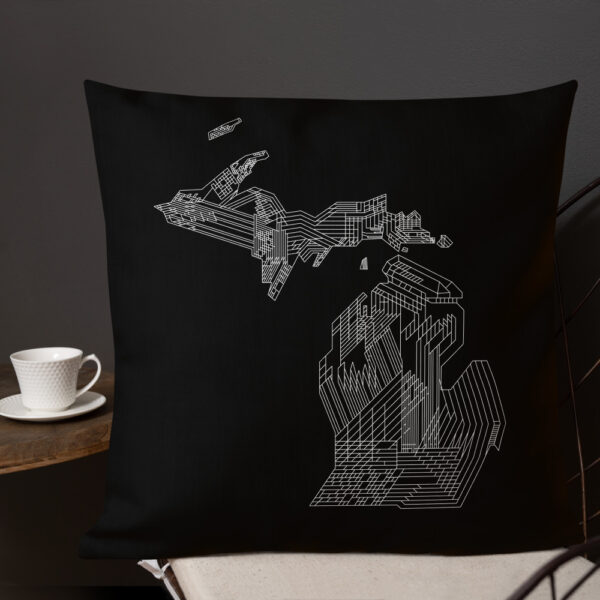 square black pillow with a white line drawing of the state of michigan, sitting on a chair next to a cup of coffee