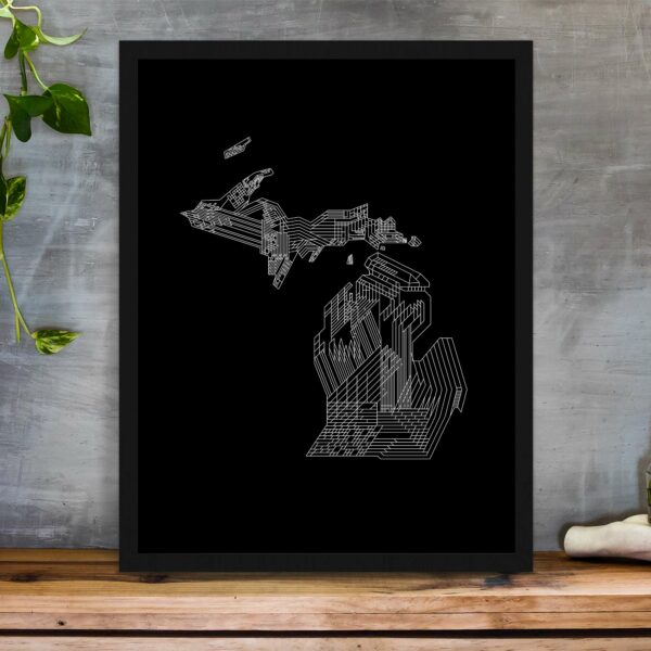 vertical fine art print with a white line drawing of the state of michigan on a black background in a black frame on a table