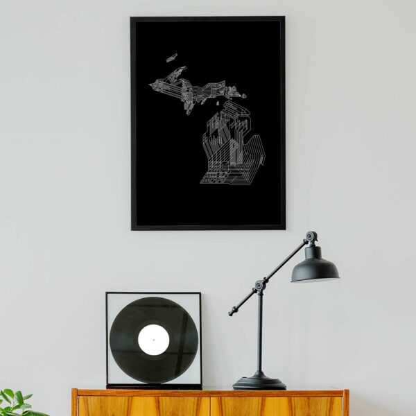 vertical fine art print with a white line drawing of the state of michigan on a black background in a black frame hanging on a wall