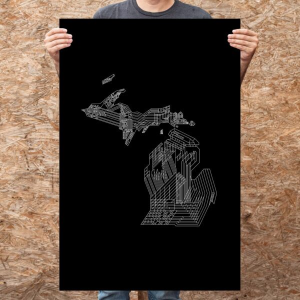 person holding a large vertical fine art print with a white line drawing of the state of michigan on a black background