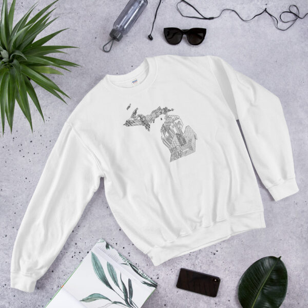 white long sleeve sweatshirt with a black line drawing of the state of michigan design laying on a table with other accessories